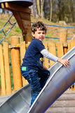 Boy playing on the slide. Boy playing on the playground on the slide royalty free stock photos