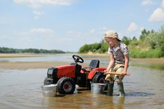 The boy is playing with tractor on the banks of the river royalty free stock photo