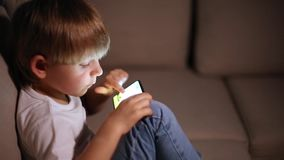 Boy playing with smart phone stock footage