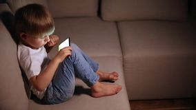 Boy playing with smart phone stock video