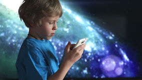Boy playing with smartphone.  boy and mobile device in hands sitting on the background of cosmic sky stock video footage
