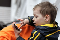 Boy playing with smartphone Royalty Free Stock Photography