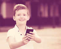 Boy playing with smartphone Stock Photography