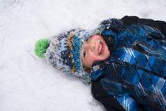Boy playing in snow angel Stock Photo