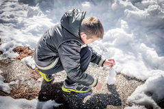 Boy playing with snow, trying to make a small snowman Stock Photo