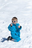 Boy playing on snow Stock Photos