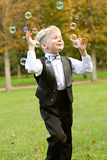 Boy playing with soap bubbles Stock Images