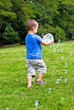 Boy playing with soap bubbles Stock Image