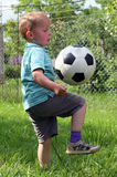 Boy playing soccer. On rustical garden Royalty Free Stock Photos