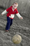Boy playing soccer. On rustical garden Stock Image