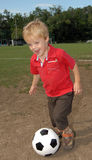 Boy playing soccer. Young boy enjoys playing soccer Royalty Free Stock Images