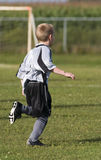 Boy playing soccer. Young soccer player running on the soccer field Stock Image