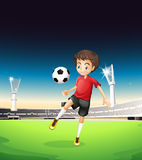 A boy playing soccer alone Stock Photography
