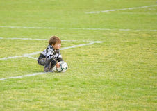 Boy Playing with Soccer Ball/Football on Field. Boy kneeling down to grasp soccerball/football on field royalty free stock image