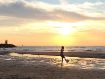 Boy playing soccer at the beach at sunset Stock Image
