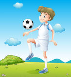 A boy playing soccer during daytime Royalty Free Stock Images