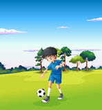 A boy playing soccer at the forest Stock Photography