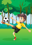 A boy playing soccer at the forest Stock Photos