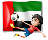 A boy playing soccer in front of the UAE flag Royalty Free Stock Images