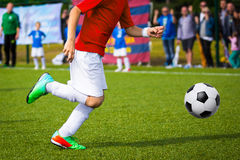Boy Playing Soccer Game. Young soccer player kicking ball on the soccer field Stock Photos