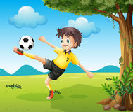 A boy playing soccer at the hill near the big tree Stock Photo