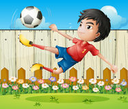 A boy playing soccer inside the fence Royalty Free Stock Images