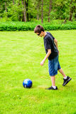 Boy playing soccer. A Boy Kicking Soccer Ball with sunglasses on Stock Photo
