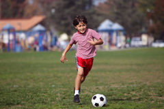 Boy playing soccer in the park Royalty Free Stock Photography