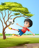 A boy playing soccer at the road Stock Image