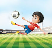 A boy playing soccer in the soccer field Stock Photos