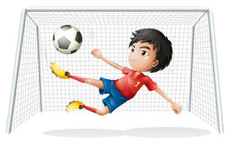 A boy playing soccer wearing a red uniform Stock Photography