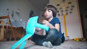 Boy is playing with soft toy in the room. A boy is playing with a soft toy in the room, against the background of a family tree stock video footage