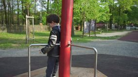 A boy is playing, spinning on a ride on a playground stock video footage