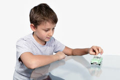 Boy playing sports retrocars on a glass table Stock Photography