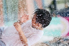 Boy playing with spraying water royalty free stock photos