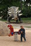 Boy playing with the spring swing with dinosaur in the backgroung Stock Photography