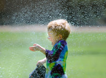 Boy playing in sprinkler Stock Image