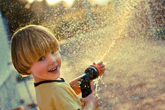 Boy playing with sprinkler Stock Images