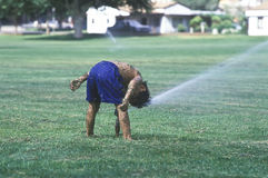 Boy playing in sprinklers. Royalty Free Stock Photography