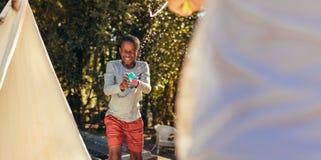 Boy playing squirt gun fight with friend. Little african boy playing squirt gun fight with friend in backyard. Kids enjoying playing water gun fight outdoors royalty free stock photography