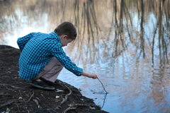 Boy playing with stick in water. Young boy playing with a stick in the river water. There is a reflection of the trees in the water. The boy is wearing a blue stock images