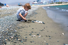 Boy playing with stones. On a beach Royalty Free Stock Images