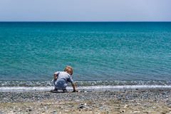 Boy playing with stones. On a beach Royalty Free Stock Photo