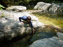 Boy playing in stream. Water flowing over rocks at Soup Bowl Pool, NH royalty free stock photography