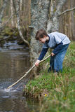 Boy playing in a stream. Young boy playing by the edge of a stream Stock Photo