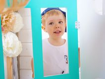 Boy playing in the studio. smiles and looks out through the decorative windows. Stock Images