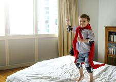 Boy playing superhero in bed stock images