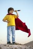 Boy playing superheroes on the sky background, child superhero i Stock Photo