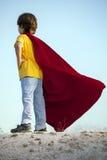 Boy playing superheroes on the sky background, child superhero i Royalty Free Stock Photography