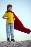 Boy playing superheroes on the sky background, child superhero i Stock Images